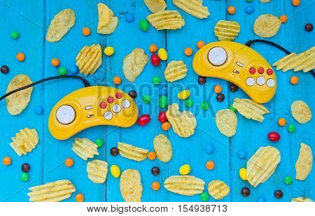 Game controller, chips and candy on a blue wooden background. fast food, snacks, not unhealthy food. Colored candy. Snack between games. Colored pills. GamePad