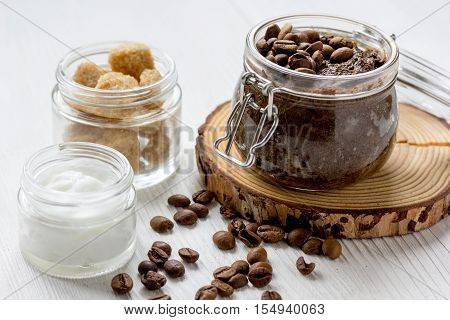 homemade coffe scrub in glass jar on wooden background.