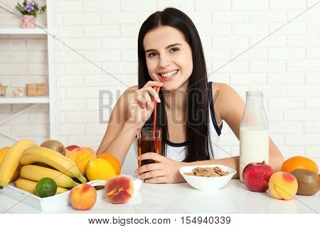 Beautiful women exists with pure skin on her face sitting at a table and eat breakfast. Asian woman eating healthy food at breakfast. Fruit, cereal and milk. Concept of natural food