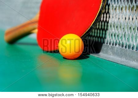 details of pingpong table with playing equipment and yellow ball