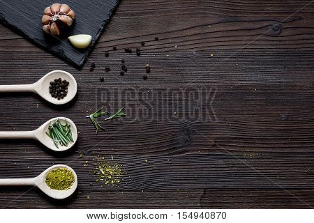 spices in spoon on dark wooden table top view