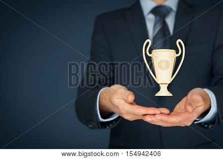 Buiness success, benchmarking and be number one on market concepts. Businessman hold cup representing success. Right composition.