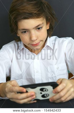 preteen handsome boy play computer games on cell phone close up photo on black background