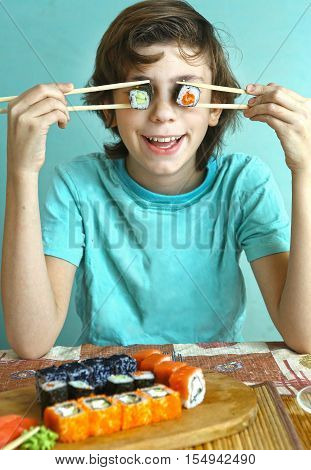 preteen boy funny portrait with suchi roll eyes close up photo on blue wall background