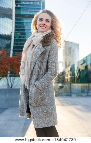 Happy blonde in long overcoat standing outside building among autumn