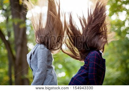 Two beautiful girls in fashionable coat waving long hair up on nature in autumn park