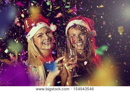 Two beautiful young girls having fun at New Year's Eve party toasting each other at midnight