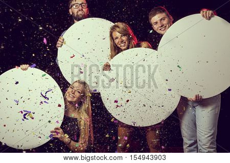 Group of beutiful young people celebrating New Year's Eve holding four blank cardboard circles