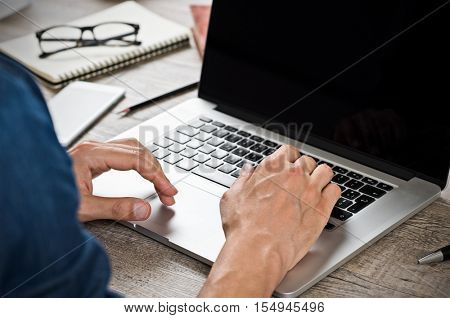 Close up of hand of businessman typing on laptop keyboard. Hand man writing an email on a laptop at office. Closeup of hand of casual business man typing on computer and sitting at wooden desk.