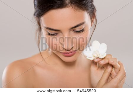 Beautiful young woman holding one orchid flower near face while looking down. Close up face of woman with healthy skin and white flowers isolated on grey background. Beauty and body care concept.