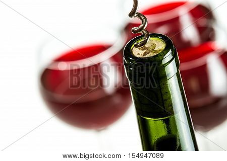 Opening green wine bottle on white background