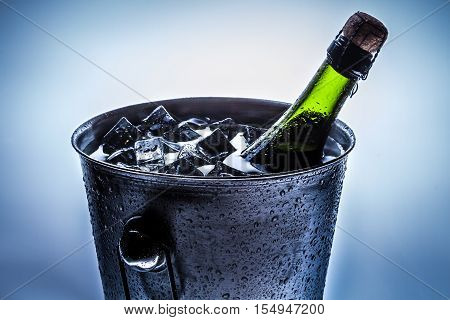 Ice cold bucket with cold champagne on white background