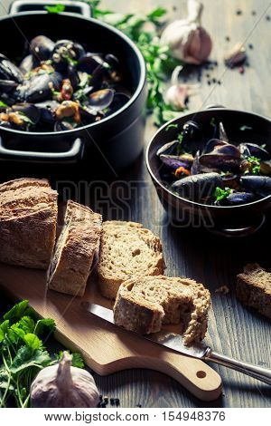 Mussels served with bread on old wooden table