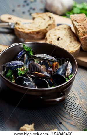 Closeup of Mussels served with bread on old wooden table