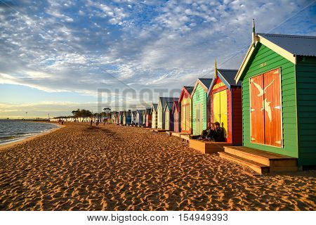 MELBOURNE AUSTRALIA - JULY 18 2016 : Tourists sit on deck of bathing boxes at Brighton Beach near Melbourne Australia.