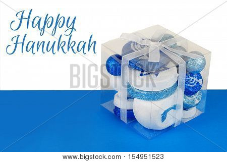 Sparkling Hanuakkah decorations in a clear plastic gift box tied with a white ribbon on a blue and white background. Happy Hanukkah message added
