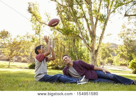 Father and son relax, throwing American football in a park
