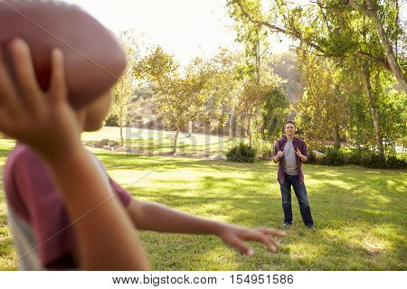Young boy throwing American football to his dad in park