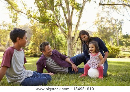 Young mixed race family relaxing with soccer ball in a park
