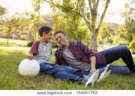 Father and son relaxing with soccer ball in a park, close up