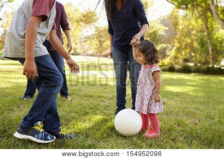 Young mixed race family playing with ball in a park, crop