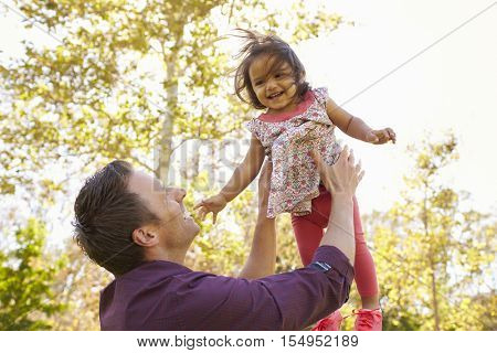 Father throwing his young daughter in the air in a park