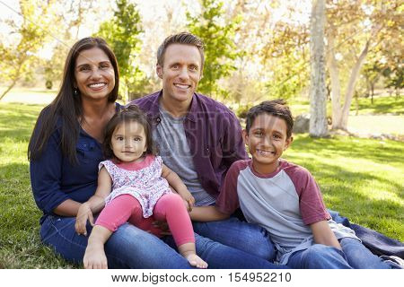 Happy Asian Caucasian mixed race family, portrait in a park
