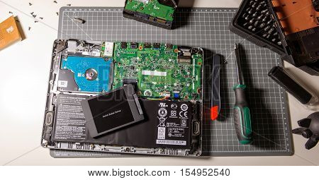 PARIS FRANCE - DEC 04 2015: Upgrade of a modern laptop PC computer to the SSD solid state drive disk for faster and better performance for writing media multimedia archives raid thunderbolt