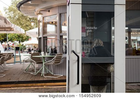KEHL GERMANY - OCT 18 2016: Deutsche Telecom phone booth with woman calling from phone booth in typical German city