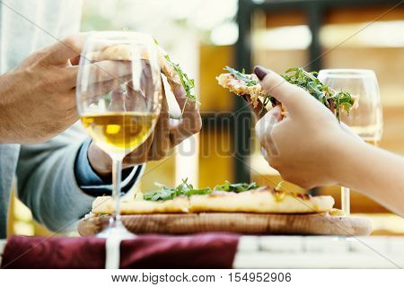 Couple in an italian restaurant eating pizza and drinking wine. Selective focus on pizza slices.