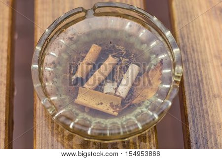 Glass ashtray with cigarette ends left in the rain with a leaf on a wooden table.