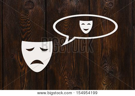 Paper sad mask is thinking about happyness. Emotion concept. Dark wooden background. Abstract conceptual image
