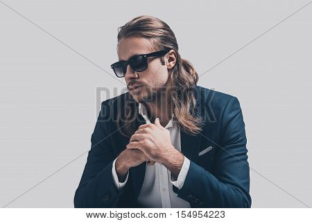 Thoughtful handsome. Handsome young man in full suit holding hands clasped looking thoughtful while sitting against grey background