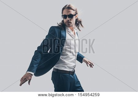 Style in motion. Handsome young man in full suit moving in front of grey background