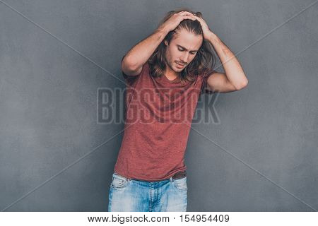 Feeling casual. Handsome young man in casual wear holding hands in hair while standing against grey background