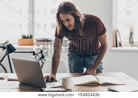 Man at work. Handsome young man with long hair looking at his laptop while leaning at the desk in creative office
