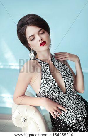 Elegant Lady. Makeup. Hairstyle. Jewelry. Brunette Sensual Woman In Fashion Gems Dress Posing On Mod