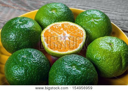 Fresh tangerines on wooden background. Sliced citrus fruit