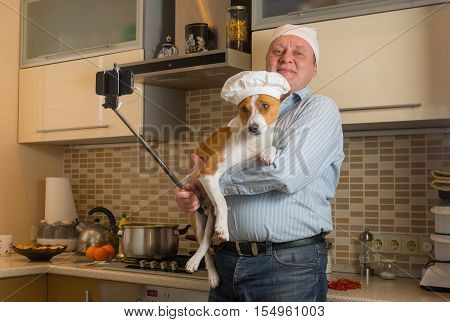 Funny mature man doing selfie in a kitchen with cute basenji dog wearing white cap