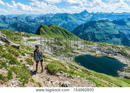 Young woman backpacking in the Grosser Daumen, Germany standing on a stony trail looking out over an alpine lake and distant rugged mountain peaks, viewed from above