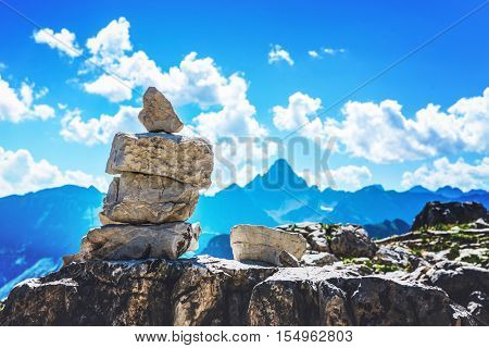 Rock cairn marking a hiking route in the Allgau alps on Grosser Daumen in Germany with a view to distant mountain peaks