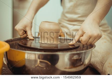 man working on the potter's wheel making the dishes with their own hands