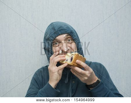 Man wearing hood greedily eating a piece of sweet cake or brownie studio cropped portrait
