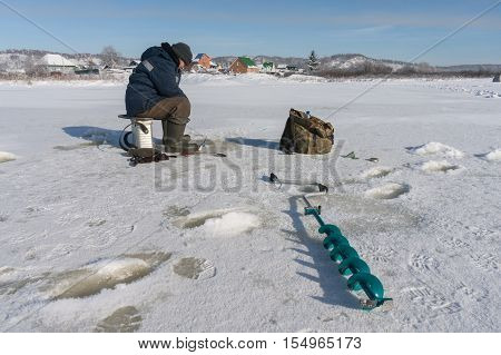 Winter fisherman on the river ice .
