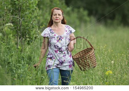 A woman with a basket is on the edge of the forest