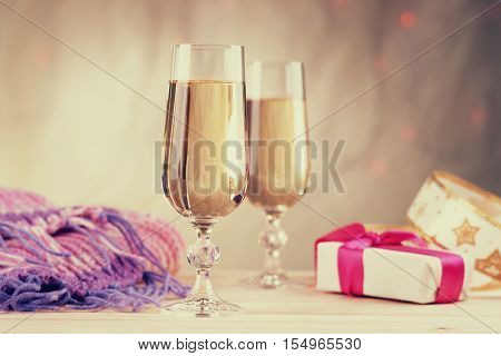 Glasses of champagne with gift box and winter scarf