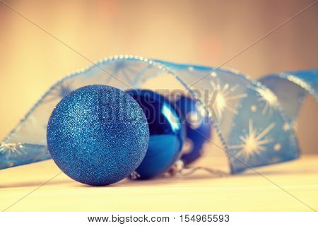 Blue christmas balls and ribbon on a table