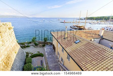 The Frankopan Castle at Kamplin square in Krk Croatia - Frankopanski Kastel part of the medieval city walls. View of the archer loop holes and sea port of the island with boats docked and ceramic tile roof houses