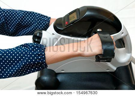 Rehabilitation muscle training for arm woman exercising on exercise bike