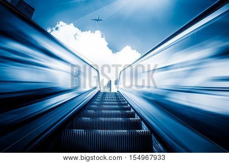 Escalator in an underground station with skyline in background.
